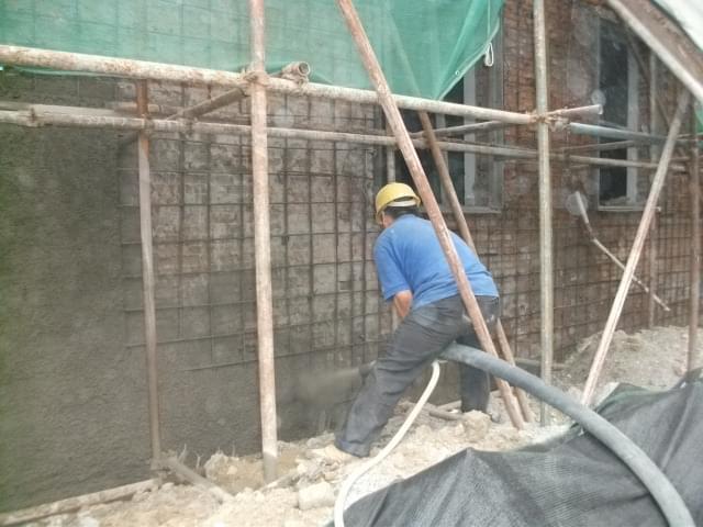 采用外包钢筋混凝土加固的方法,其施工工艺流程如下: (1)清理基层:清除砖柱上的管线和装饰层,检查柱根;剔除损坏的砖,清除裂缝内的粉尘。 (2)根据不同的加固形式,采用不同的连接措施。单侧加固时,用混凝土钉或膨胀螺栓连接;双面加固时,用封闭箍筋连接。当柱较宽时,沿高度每隔5皮打掉一块,增强混凝土与原柱的咬合,有利于共同受力。 (3)绑扎钢筋:用外包钢筋混凝土加固,绑扎的钢筋应与砖柱固定牢靠,控制好位置和保护层厚度。 (4)浇筑混凝土:外包混凝土加固宜用喷射法施工,具体步骤参照第2.